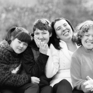 Group of women embracing and smiling.