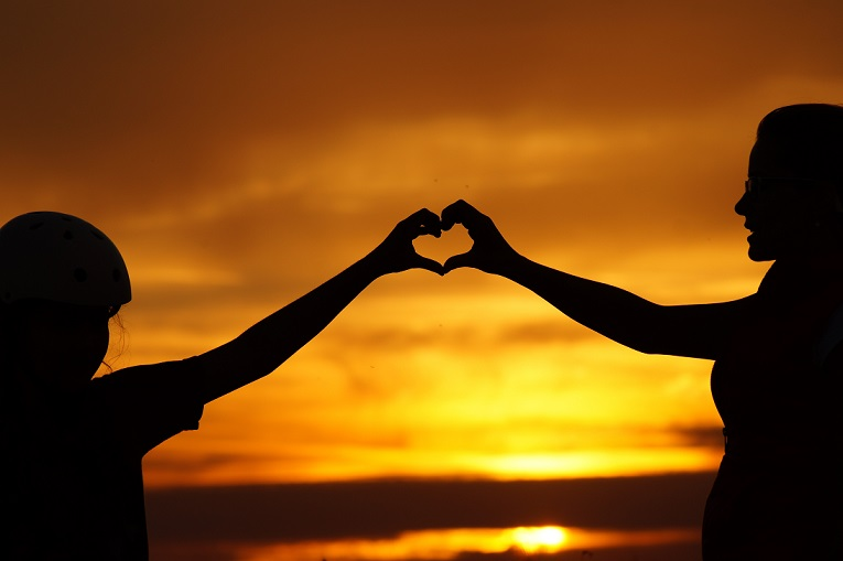 Silhouette of two people forming a heart with their hands.