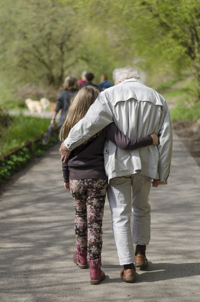older man and grandchild walk side by side in a park