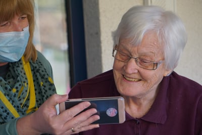 Elderly woman smiles at a phone that a younger woman is showing her.