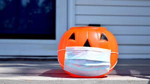 Pumpkin candy holder with a mask covering its face.