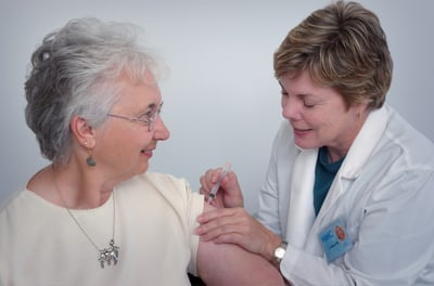 Doctor gives elderly lady a shot.