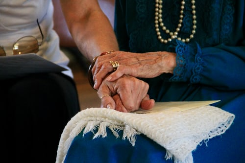Elderly people holding hands.
