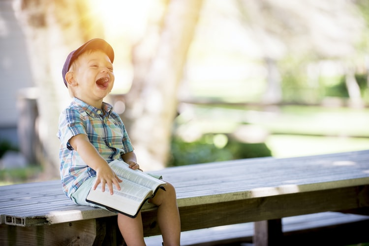 Little boy laughing while holding a book.